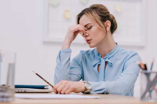 exhausted adult business woman sitting at her desk holding the bridge of her nose