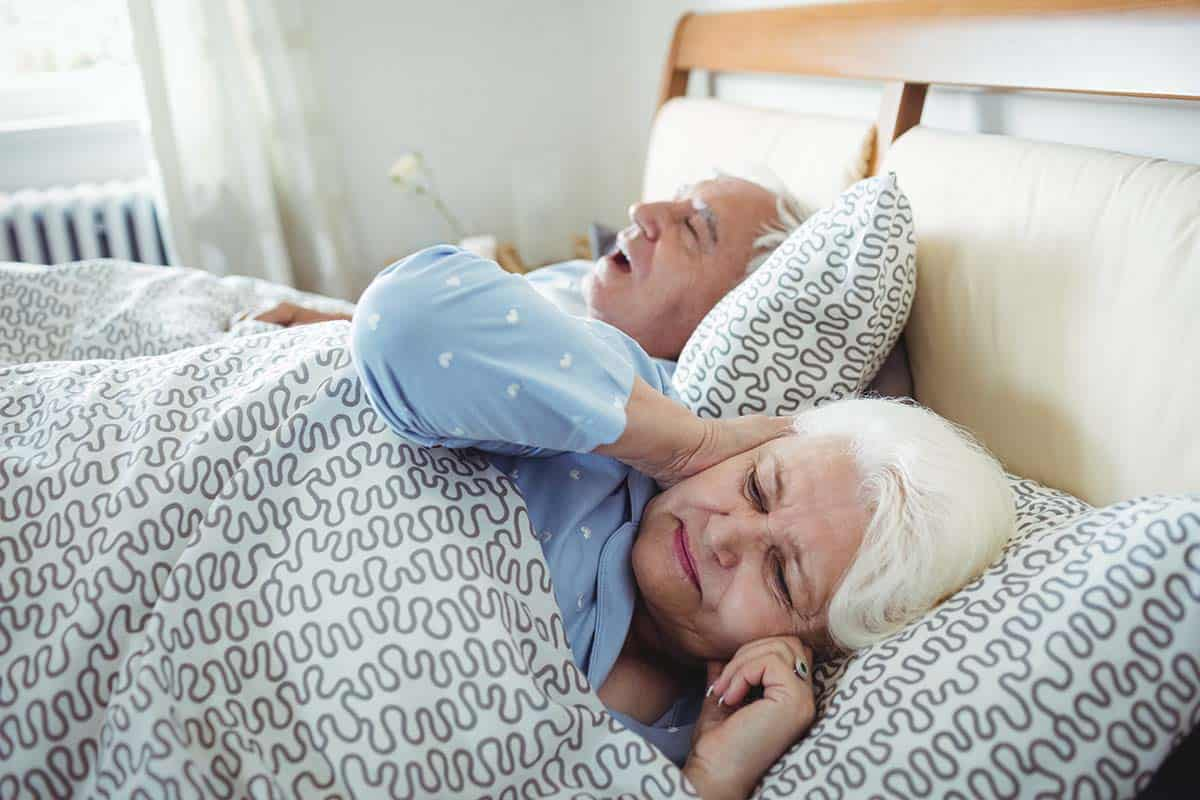 man snoring in bed with woman covering her ears next to him