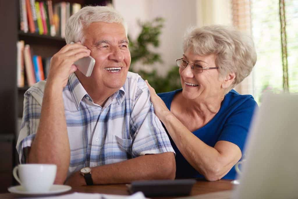 Old man talking on the phone at the table with his wife sitting next to him